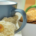 knitting traditions passed down to children from older generations. Blue cup with cream knitted cup holder and biscuits.