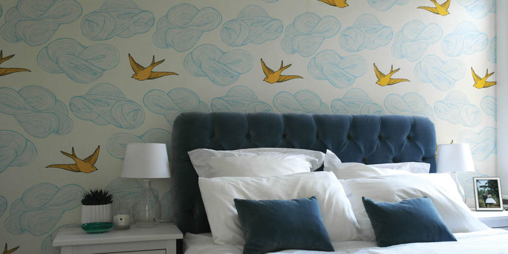 Yellow and blue bird wallpaper and blue headboard
