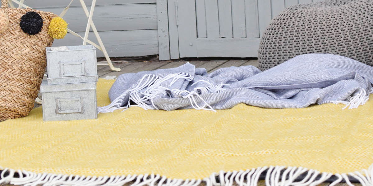 Picnic set up with yellow wool blanket and picnic basket